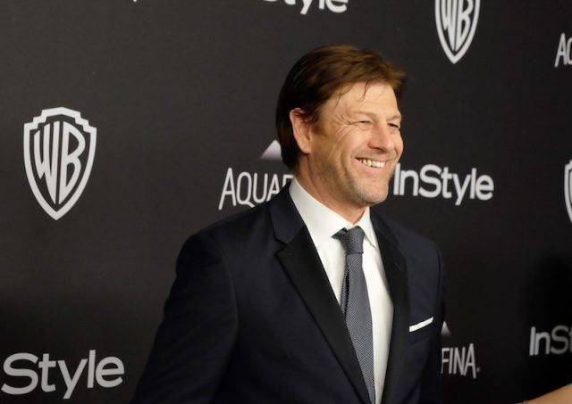 Sean Bean smiling while posing on a red carpet in a black suit and tie.