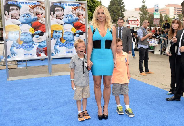 Britney Spears and her two sons on a red carpet.