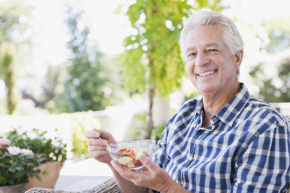Senior man eating vegetables on a patio