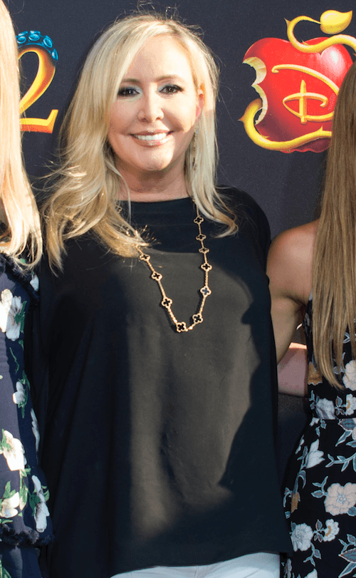 Shannon posing on a red carpet in a black shirt and white pants.