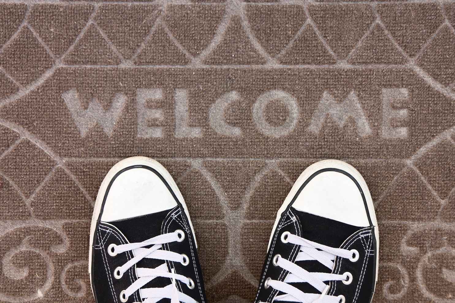 Welcome carpet with black converse sneakers