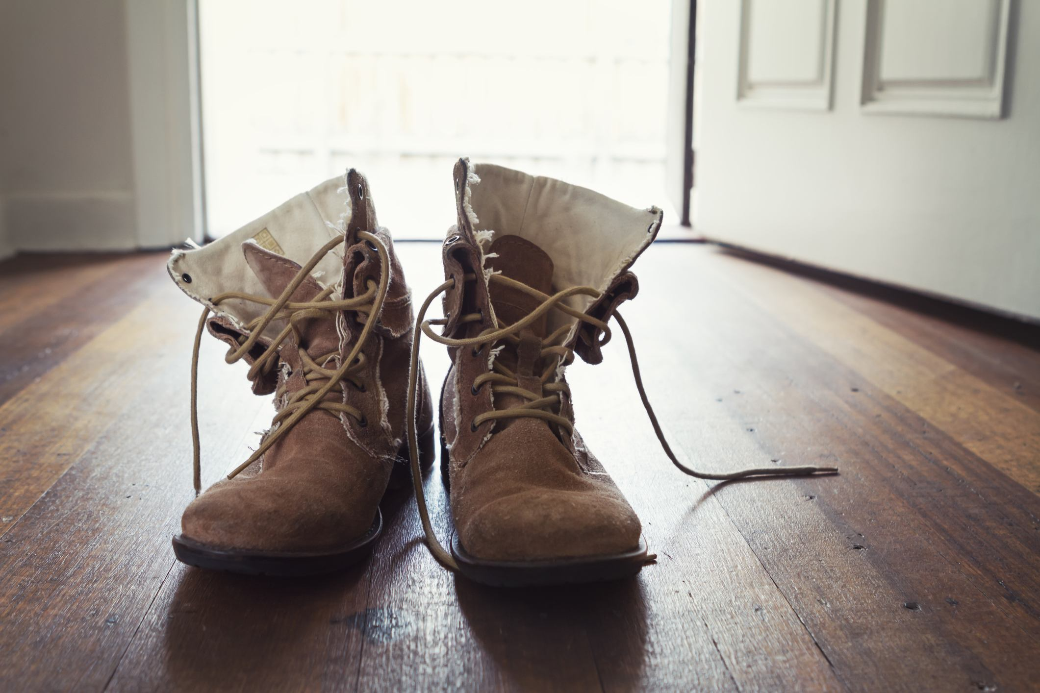 Pair of men's worn leather shoes or boots in doorway of home