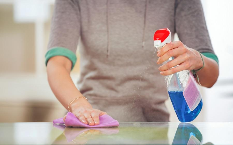 Woman cleans a glass table with a spray