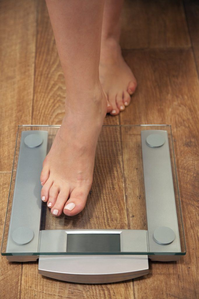 woman stepping on weight scale