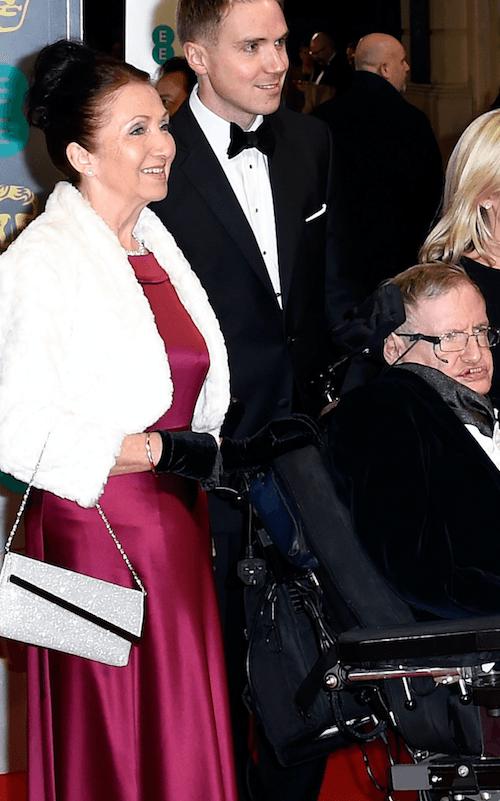 Jane Wilde standing behind Stephen Hawking.