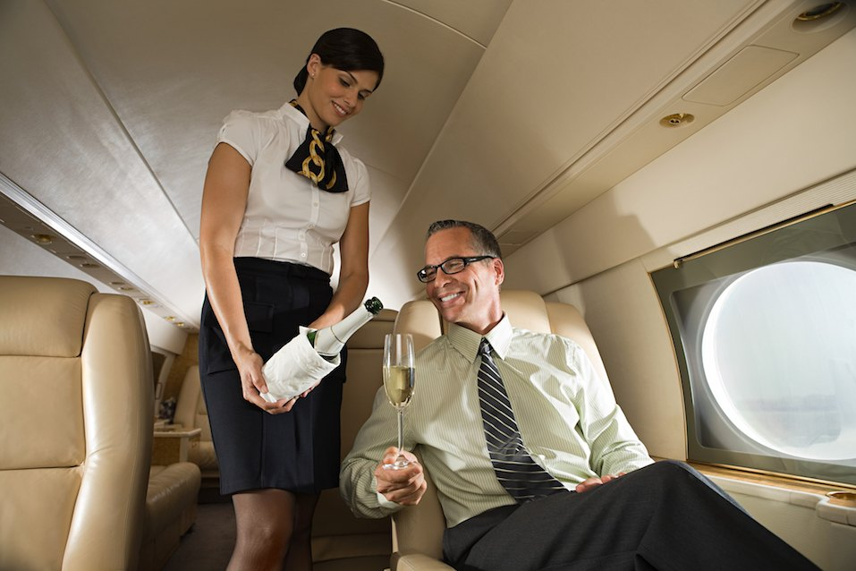 Stewardess pouring wine for man