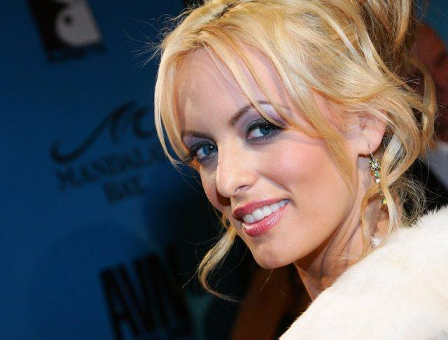 Stormy Daniels smiling and posing on a red carpet.