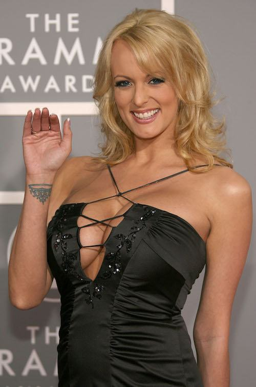Stormy Daniels smiling and waving on red carpet.