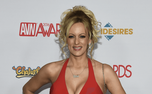 Stormy Daniels wears red dress on a red carpet.