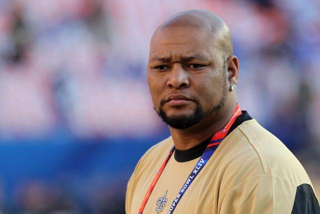 Former New Orleans Saints player Deuce McAllister watches teams warm up on the field