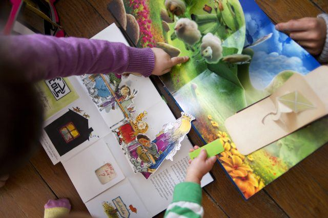 Children read pop-up books, three-dimensional or movable books