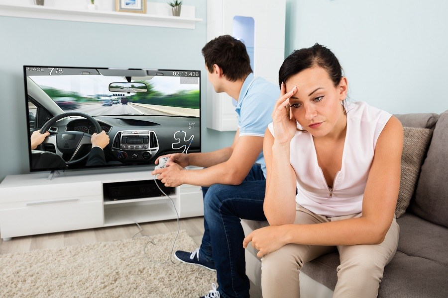 Man playing a video game while a woman sits next to him looking upset