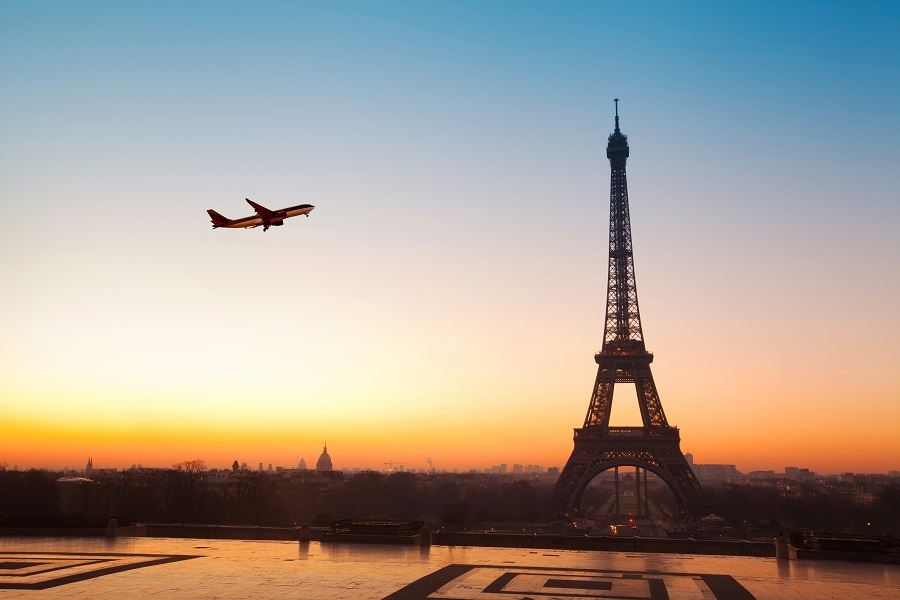 Eiffel tower at sunrise and airplane in the blue sky