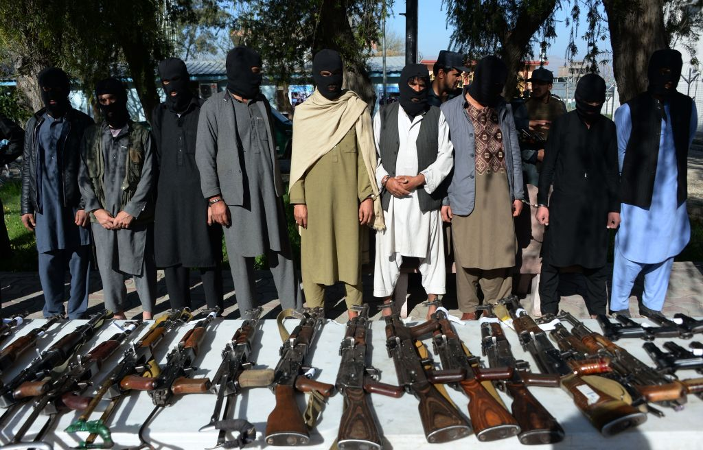 Taliban members in handcuffs with guns in front