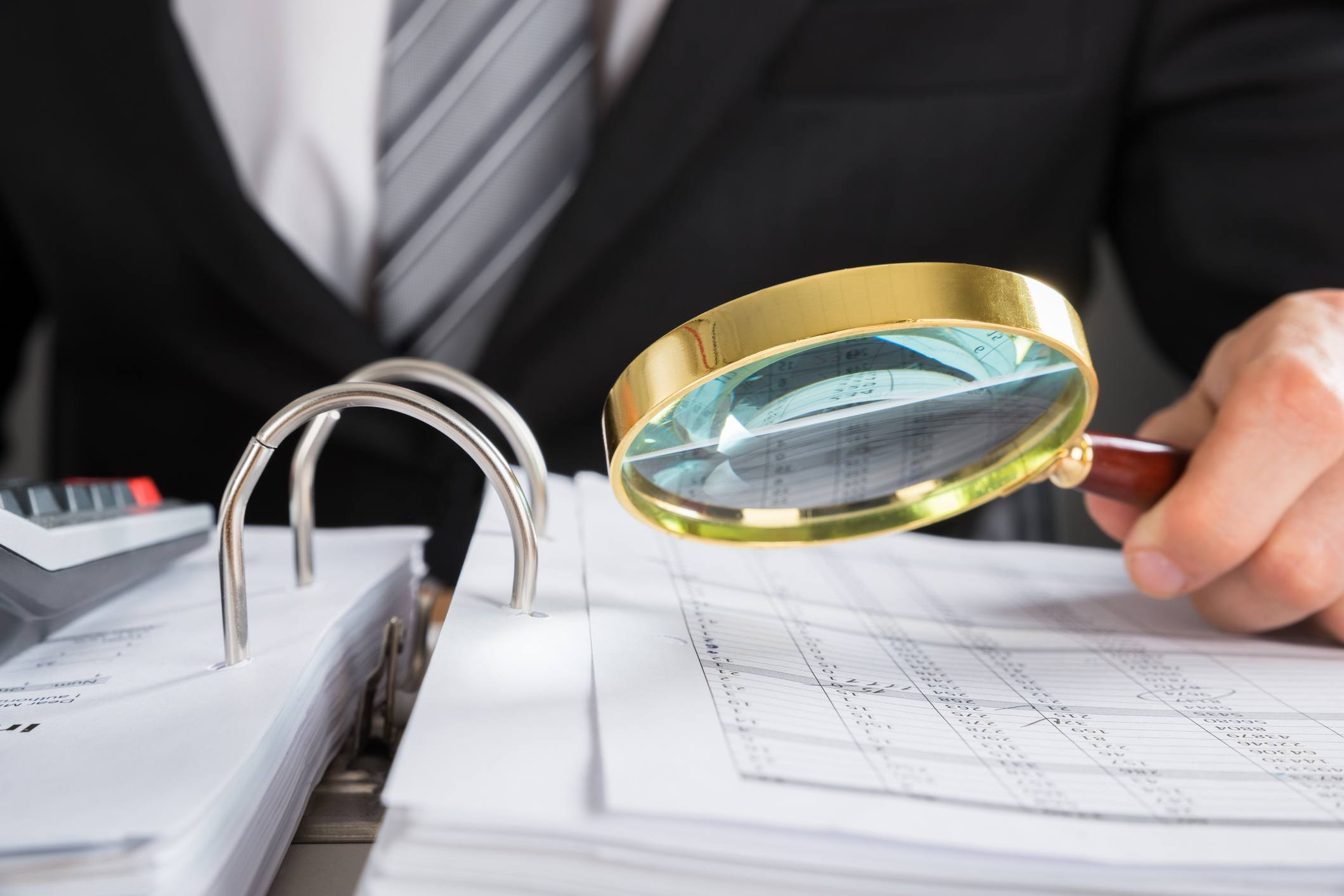 Examining tax audit with magnifying glass