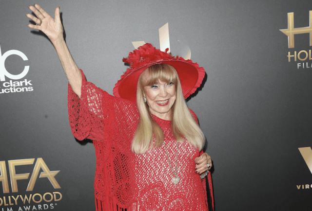 Terry Moore waving while on a red carpet.