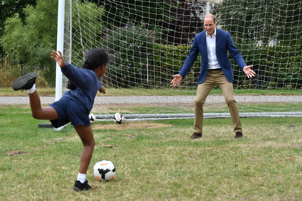 Prince William, Duke of Cambridge takes his turn in goal up against a member of the Wildcats Girl' Football programme