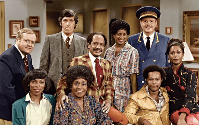 The cast of 'The Jeffersons' standing together in a living room.
