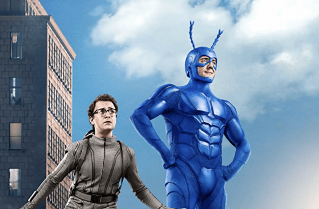 The Tick poses on top of a building.
