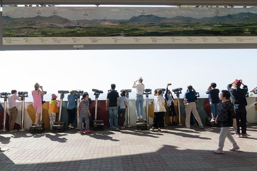 Tourists watching with binoculars to North Korean village Propaganda village or Peace village at Korean Demilitarized Zone