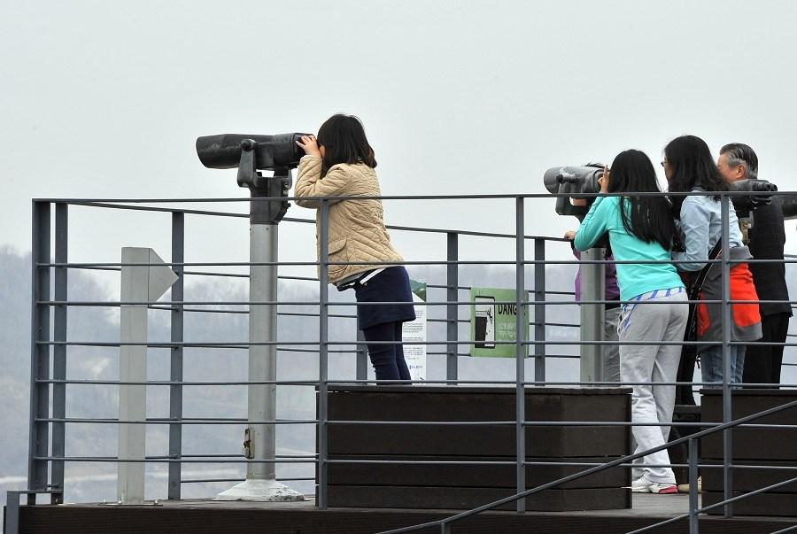 Tourists watching with binoculars at Korean