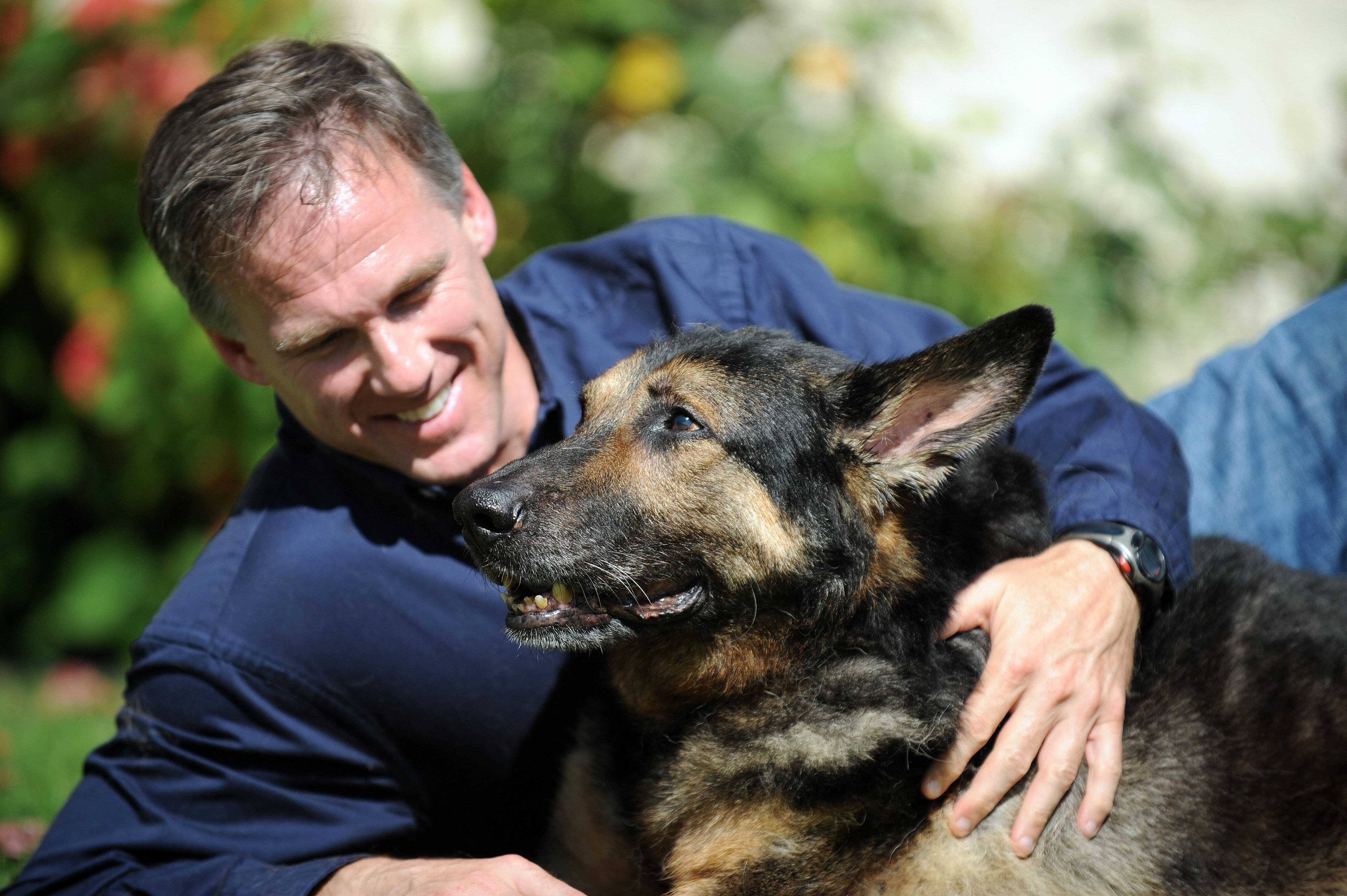 Trakr search and rescue dog lays with his owner