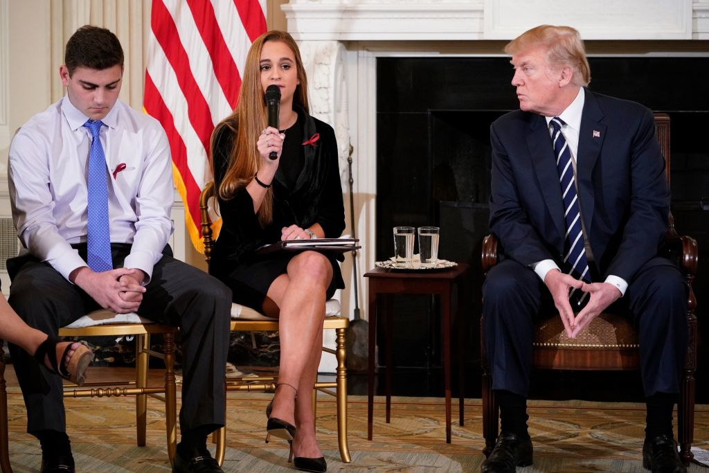 President Donald Trump (R) watches as Julia Cordover (C), Parkland student body president, speaks during a listening session on gun violence