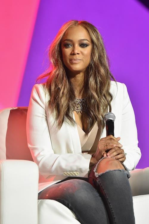 Tyra Banks sits in a white blazer while holding a microphone.