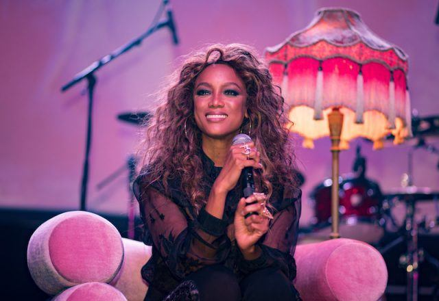 Tyra Banks sits on a pink chair while on stage.