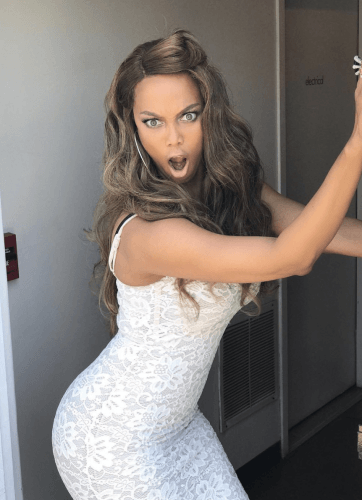 Tyra Banks posing for a photos in w white dress.