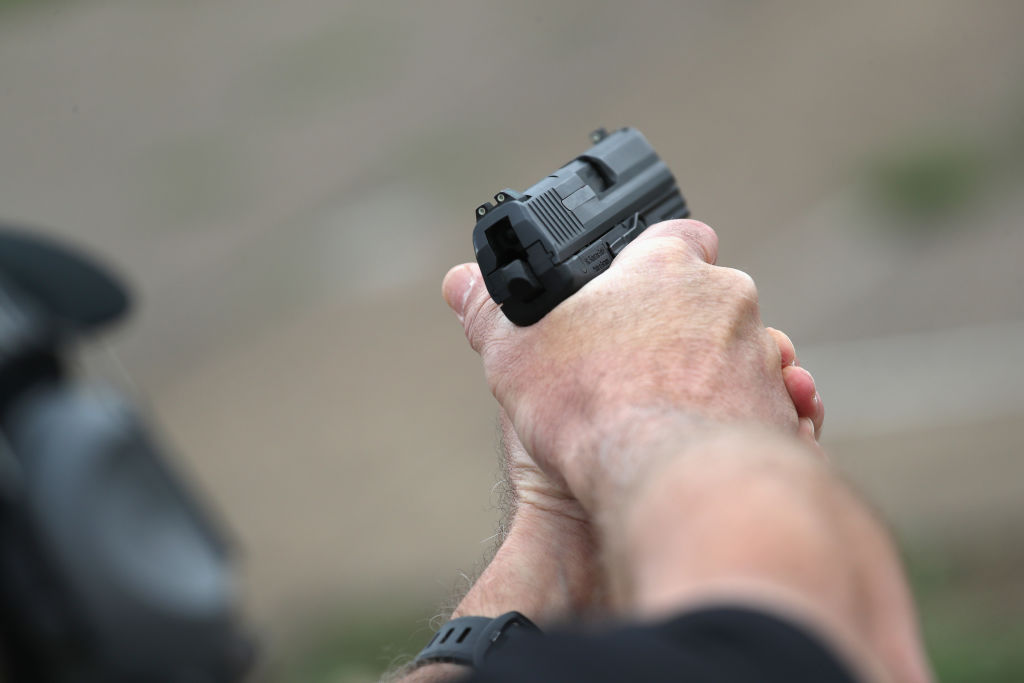A U.S. Customs and Border Protection agent fires an H&K P2000 handgun