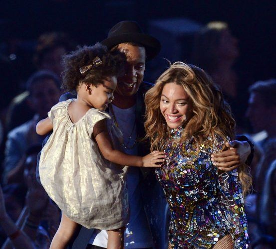 Recording artist Jay-Z holding their daughter Blue Ivy Carter hugs Beyonce on stage at the MTV Video