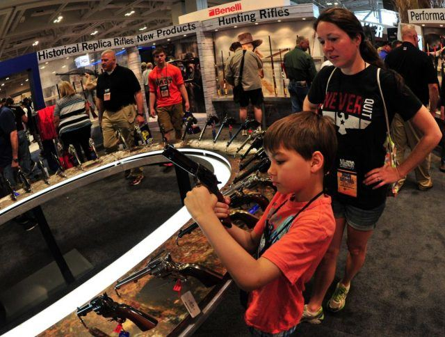 Convention goers look at old west handguns at the A. Uberti booth