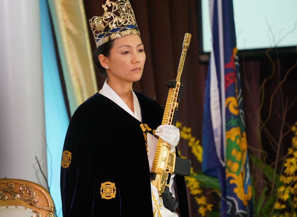 Rev. Yeon Ah Lee Moon, wife of Rev. Hyung Jin Moon, holds weapon as worshippers at World Peace and Unification Sanctuary attend services