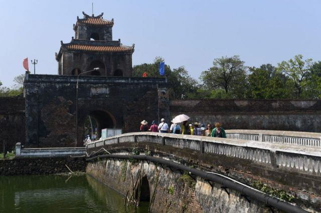 Tourists walk on a bridge leading to the former imperial citadel Vietnam's former imperial city