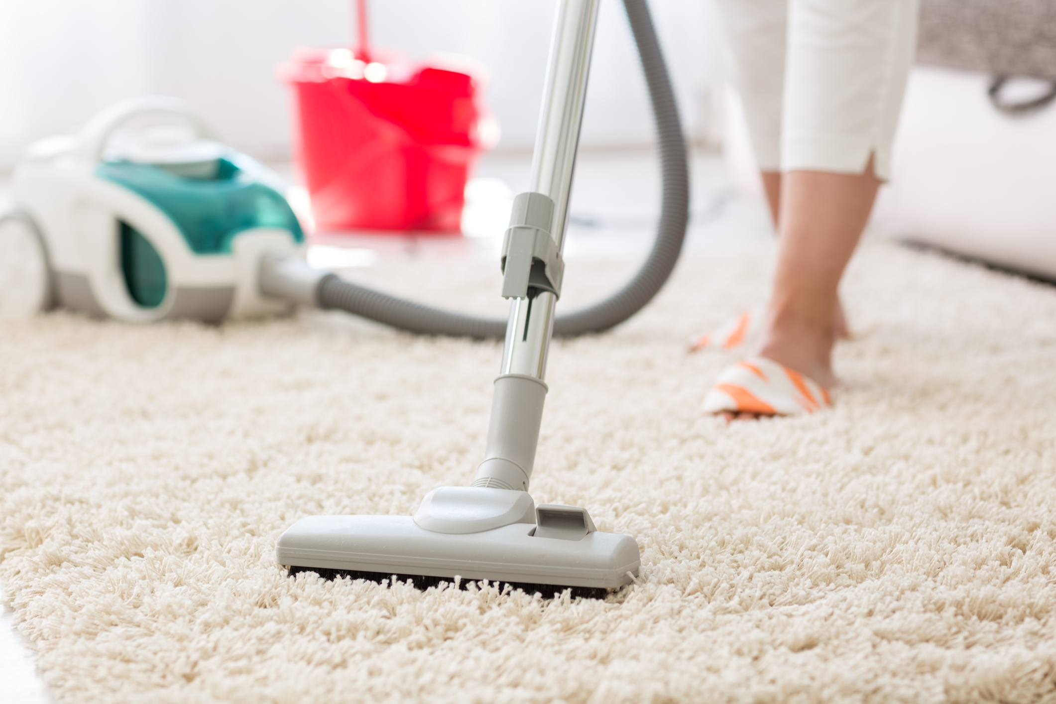 Woman Vacuuming a beige carpet