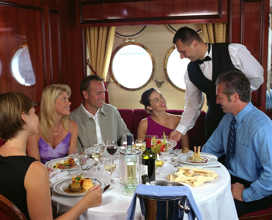 Waiter serving table of five in a cruise ship