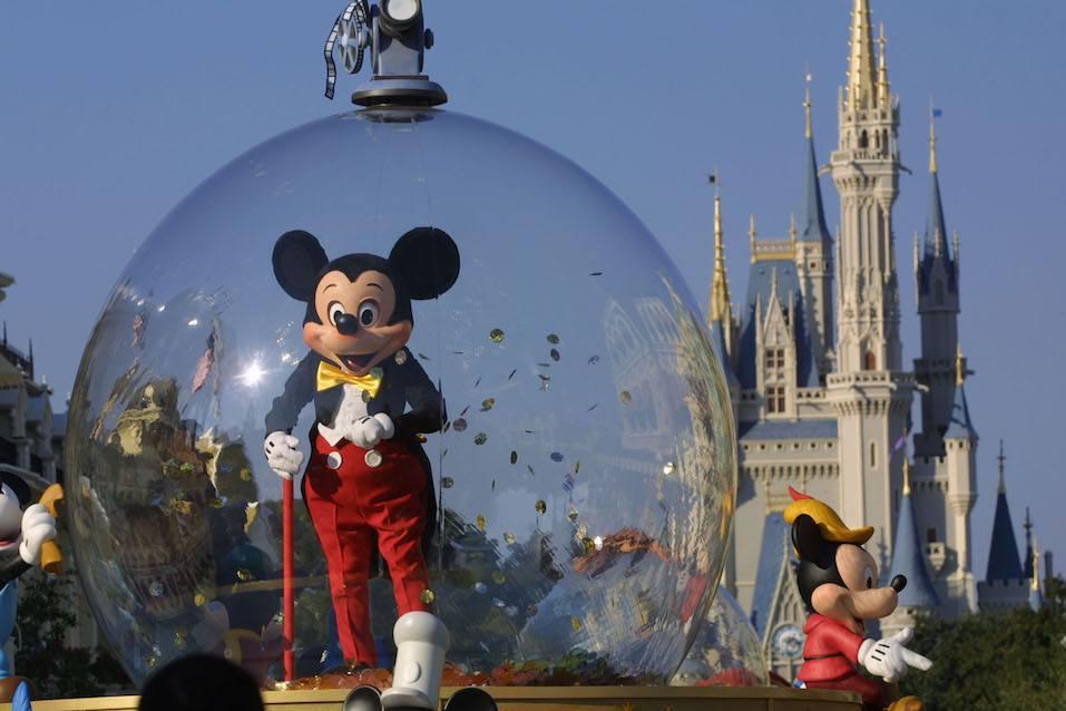 Mickey Mouse rides in a parade through Main Street
