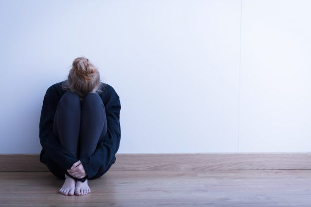 Woman sitting alone and worried in her rorom