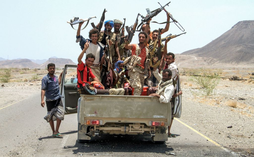 Rebels in a truck waving guns in the air