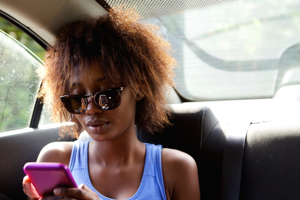 Woman sitting in backseat of car looking at cell phone