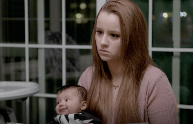 A young woman on 'Young and Pregnant' holds her baby while looking serious.