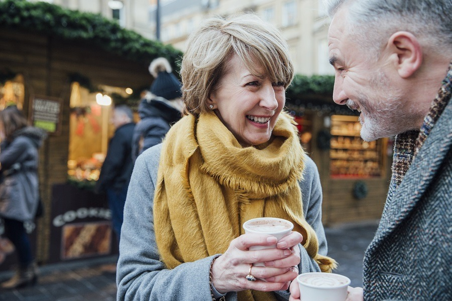 Mature couple are enjoying a cup of coffee as they explore the town christmas market.
