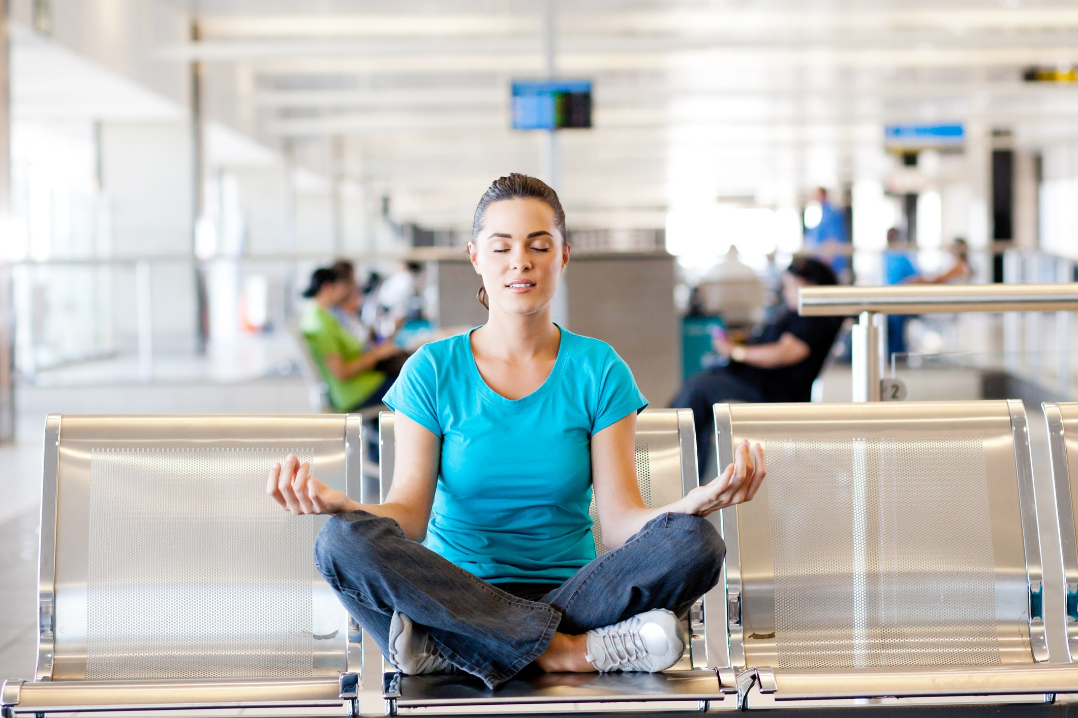 woman does yoga in an airport terminal