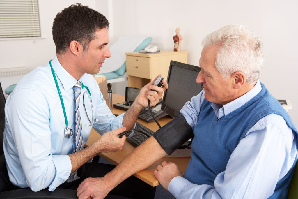 Doctor taking senior man's blood pressure