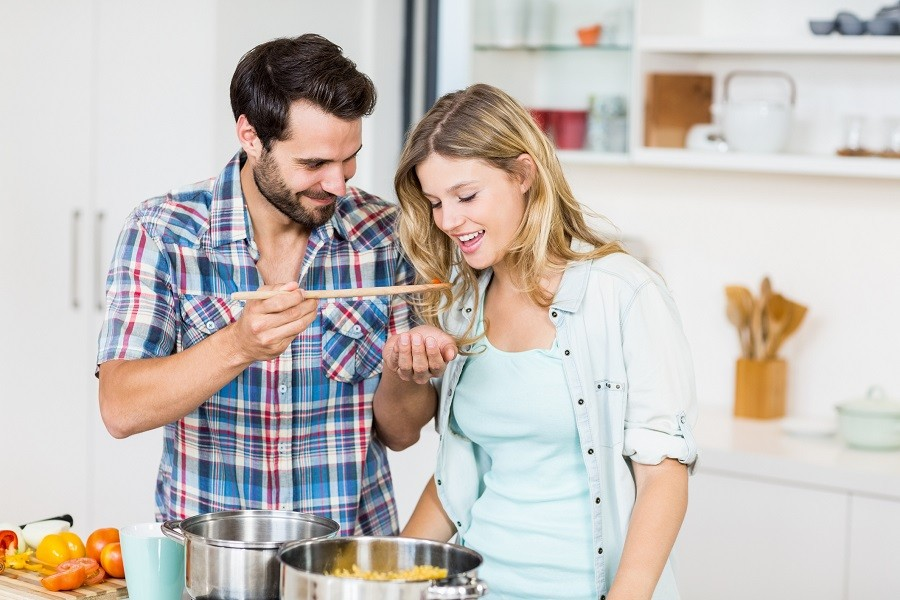 Young couple tasting food in the kitchen
