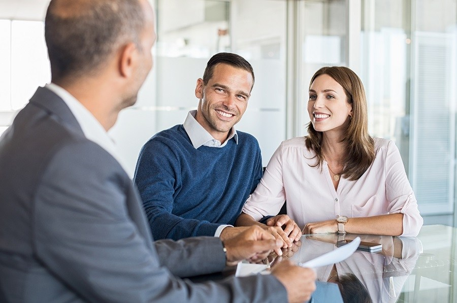 Mature financial advisor showing report to young couple