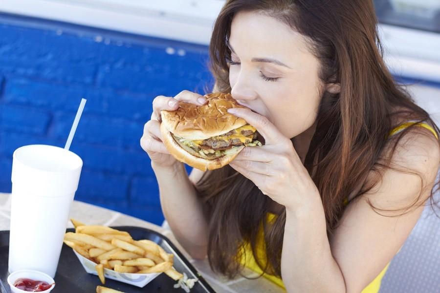 A woman enjoys a hamburger.