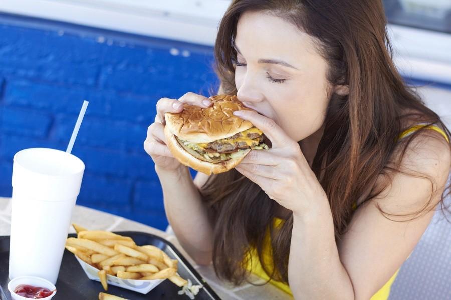 A woman enjoys a hamburger.