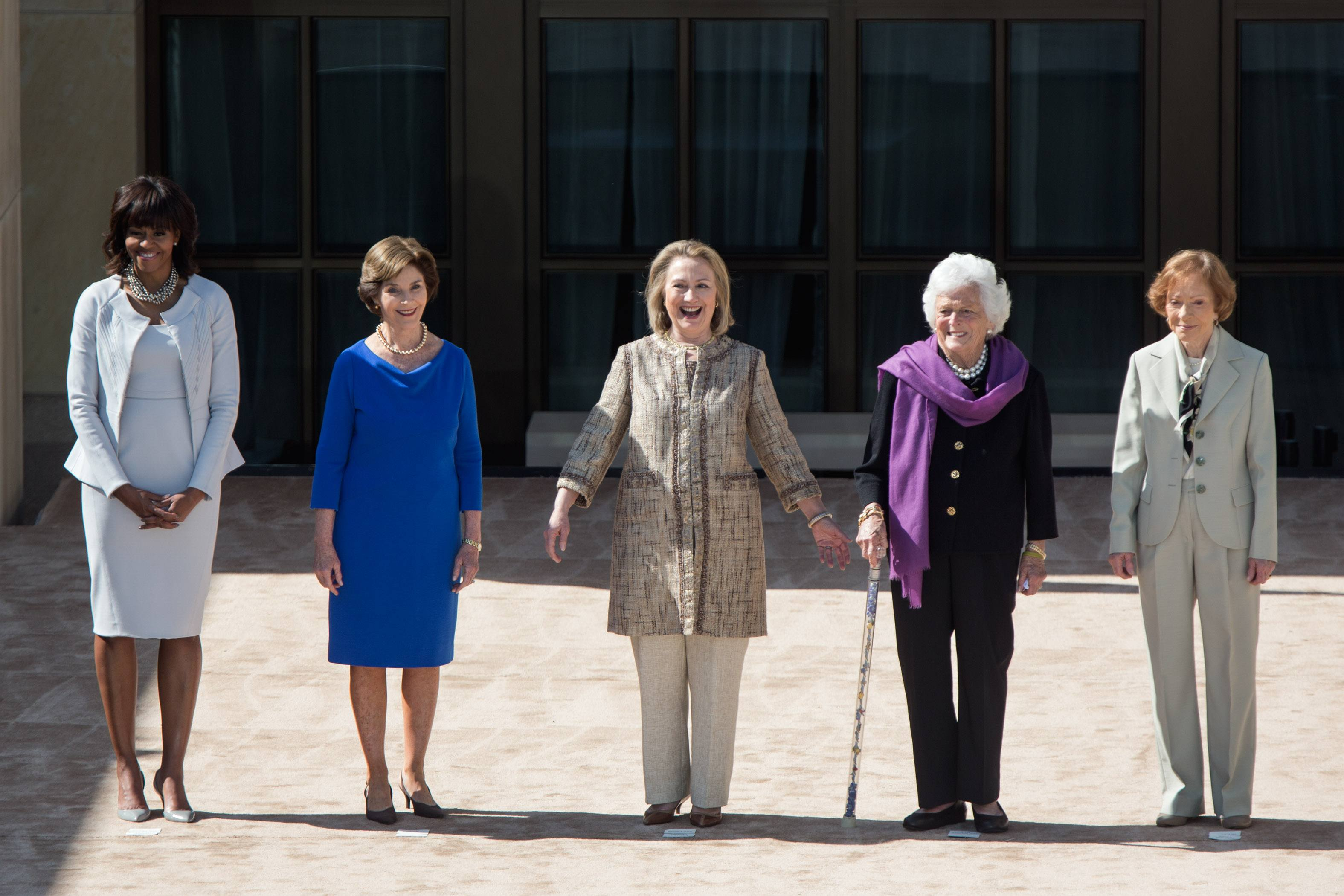 First Lady Michelle Obama pauses with former First Ladies Laura Bush, Hillary Rodham Clinton, Barbara Bush, and Rosalynn Carter during the dedication of the George W. Bush Presidential Library and Museum on the campus of Southern Methodist University in Dallas, Texas, April 25, 2013.